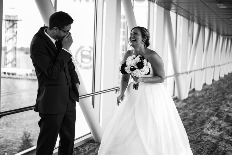 Bride and groom laughing during first look at Sheraton Erie Bayfront Hotel wedding