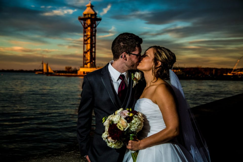 Bride and groom kissing with Bicentennial Tower and Lettie G Howard sailing in the background