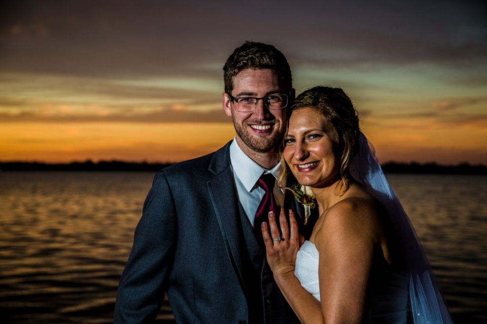 Bride and groom smiling at sunset on Lake Erie