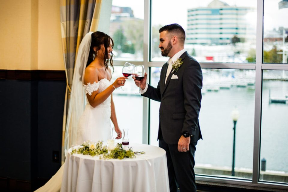 Bride and groom toasting wine during unity ceremony at Sheraton Erie Bayfront Hotel