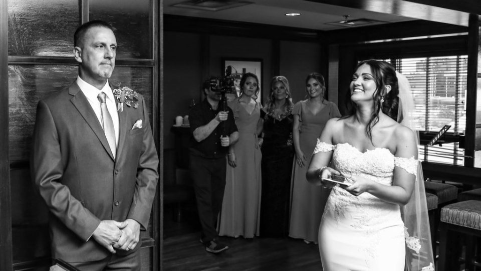Bride sneaks up on her father during first look at downtown Erie wedding