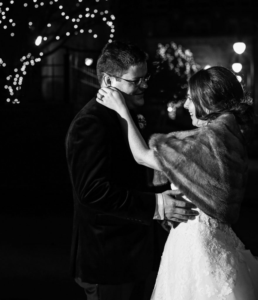 Bride strokes groom's cheek outside Washington and Jefferson College at night