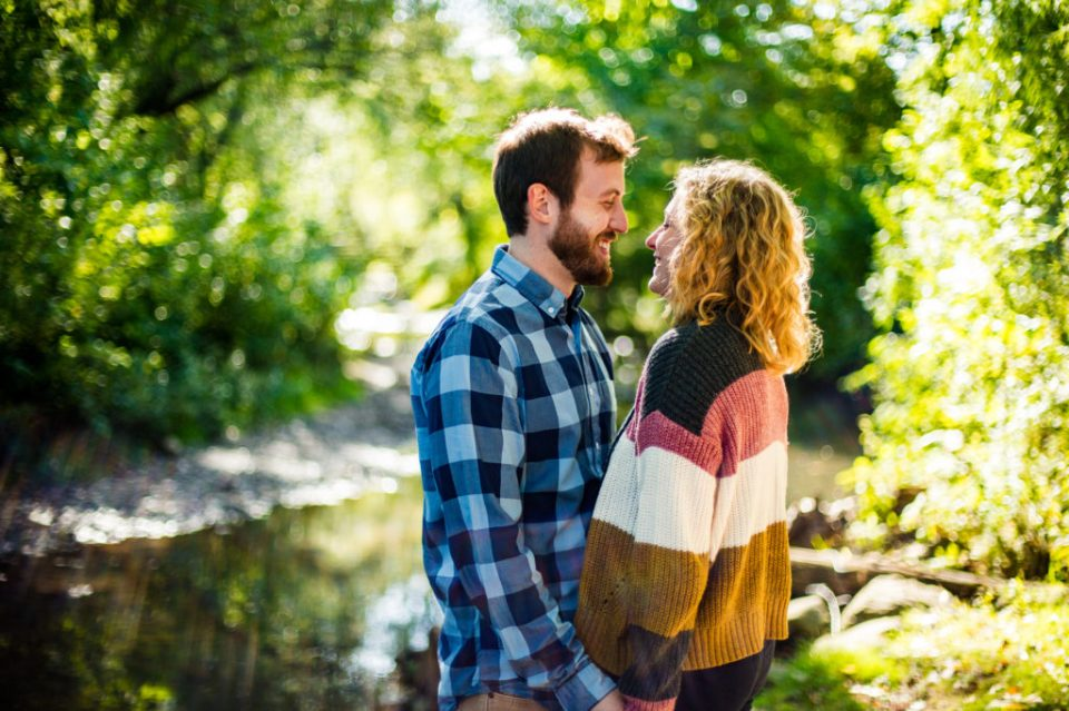 Couple smiles at each other next to Cascade Creek in Frontier Park