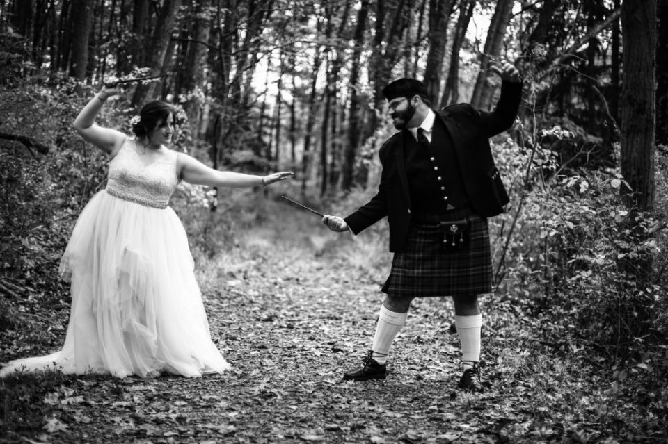 Bride and groom pointing magic wands at each other at Bushy Run Battlefield