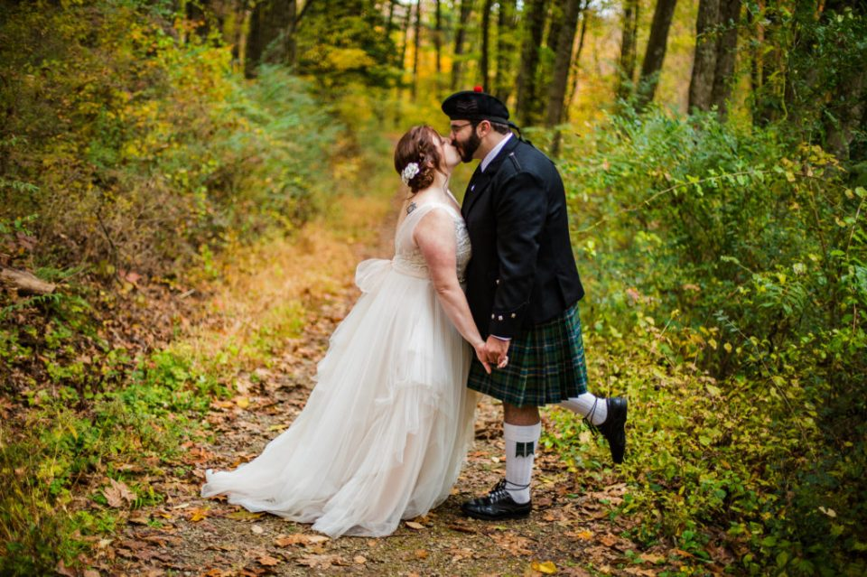 Bride and groom kissing on a walking path at Bushy Run Battlefield