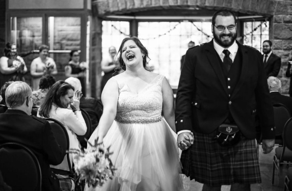 Bride laughing as she and groom exit wedding at Bushy Run Battlefield