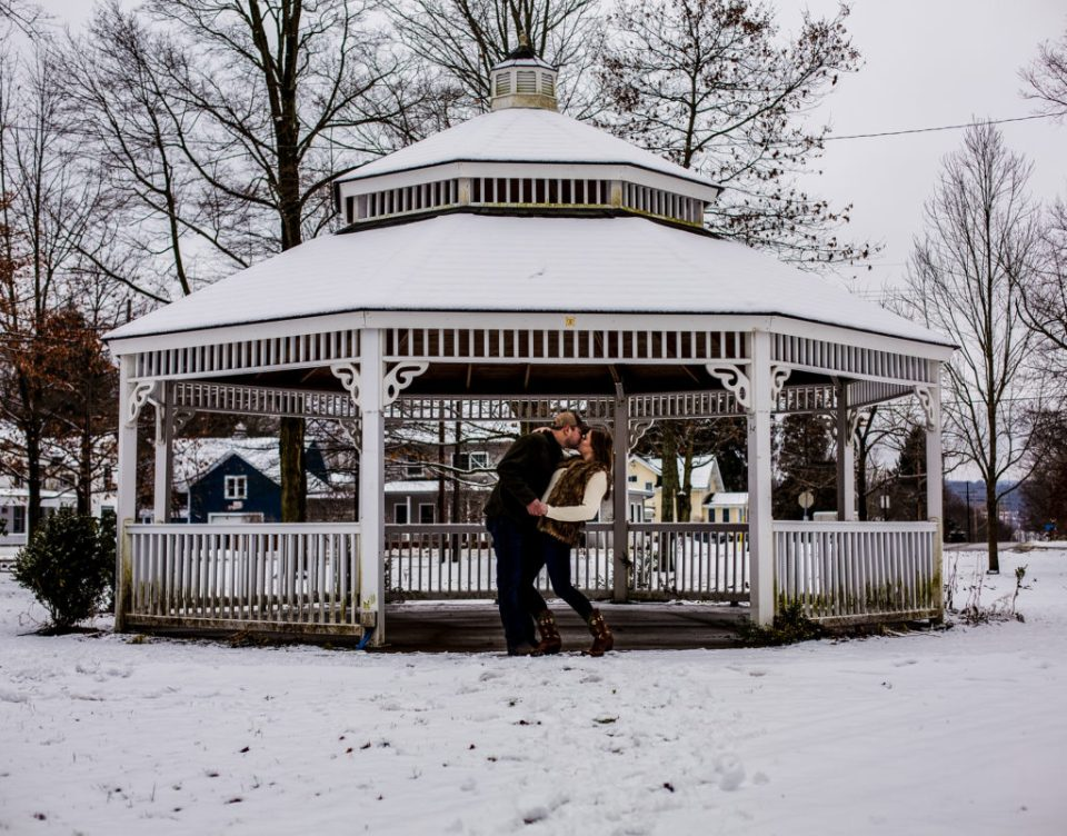 Couple kisses in front of a gazebo in a park in downtown Waterford, PA