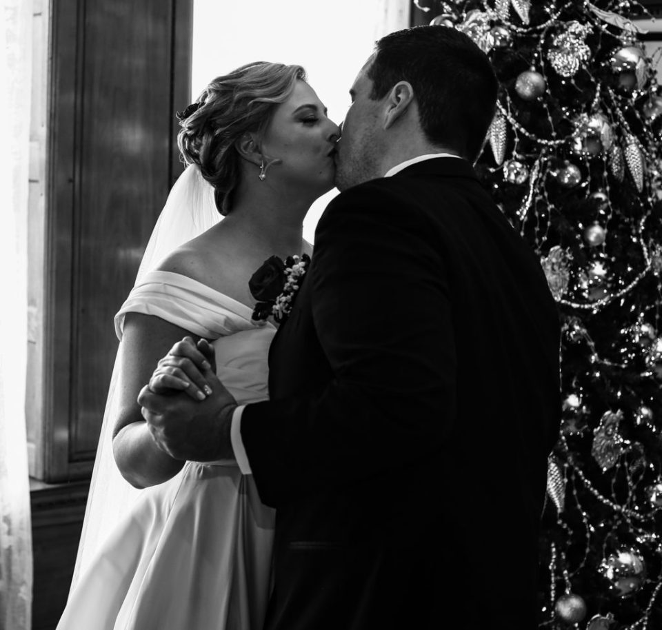 Couple kissing next to Christmas tree at Watson Curtze Mansion