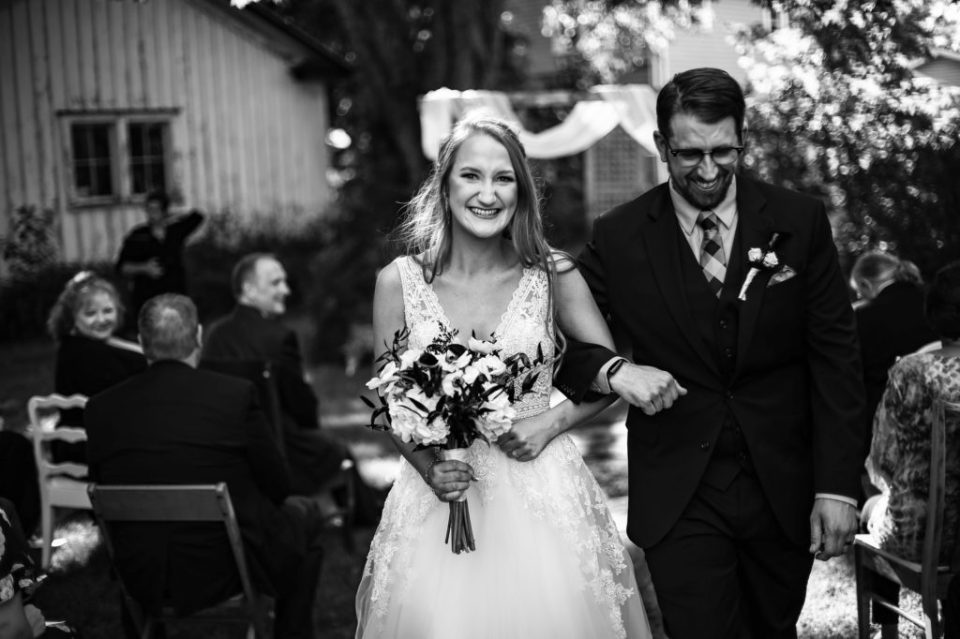 Recessional portrait of couple at their intimate backyard wedding