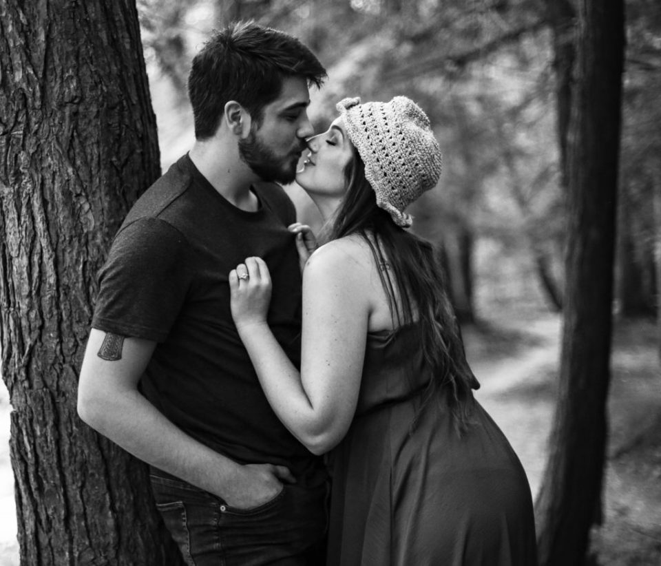 During engagement photos at Wintergreen Gorge woman leans in to kiss man leaning against a tree