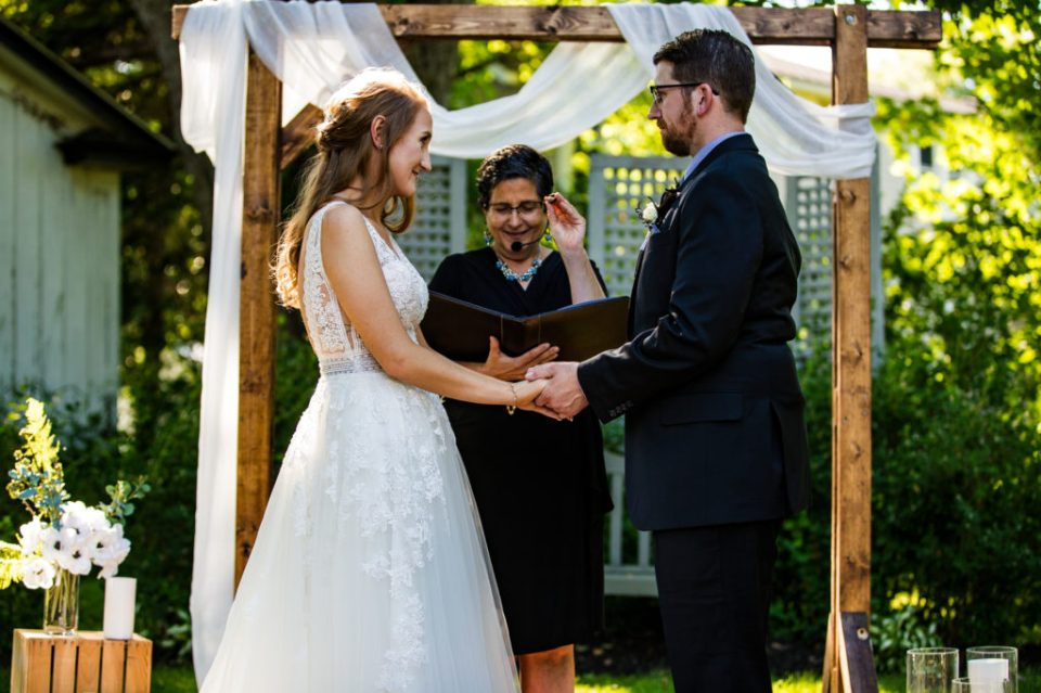 Man and woman exchange vows in an intimate backyard wedding at their home