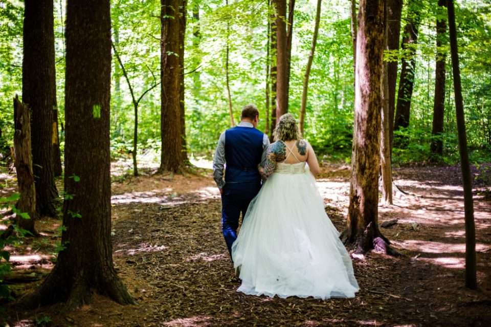 Bride and groom walking through Asbury Woods for anniversary photos