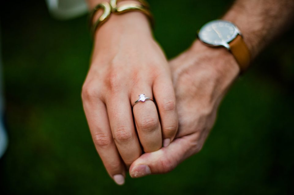 Photo of woman and man's hands with focus on engagement ring