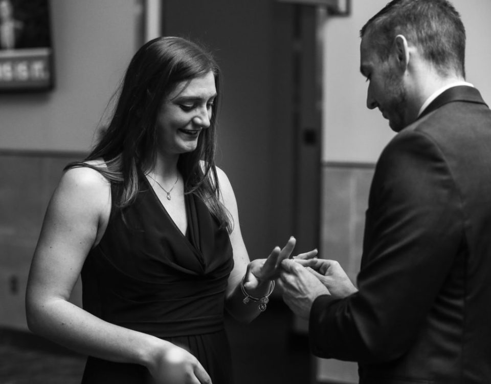 Man puts engagement ring on woman's finger during proposal phots at Bayfront Convention Center