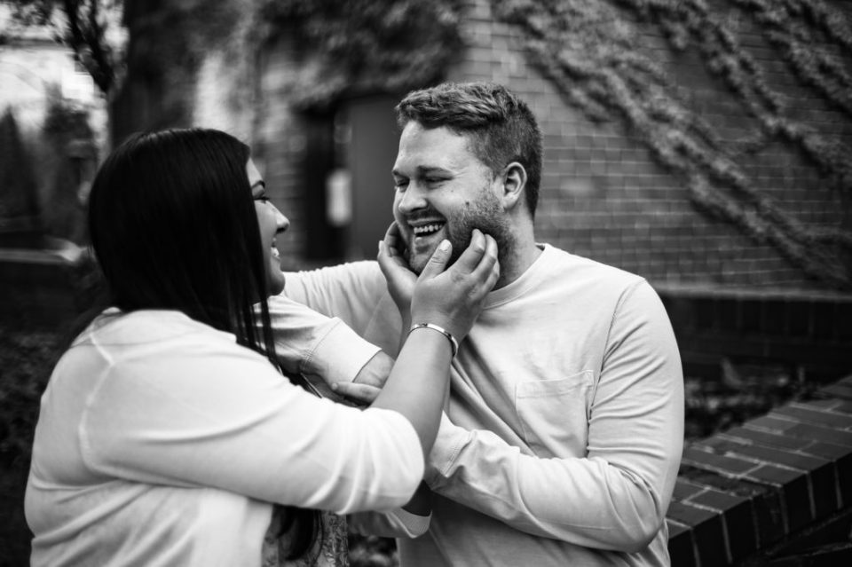 woman touches fiance's cheeks during Erie Bayfront engagement photos