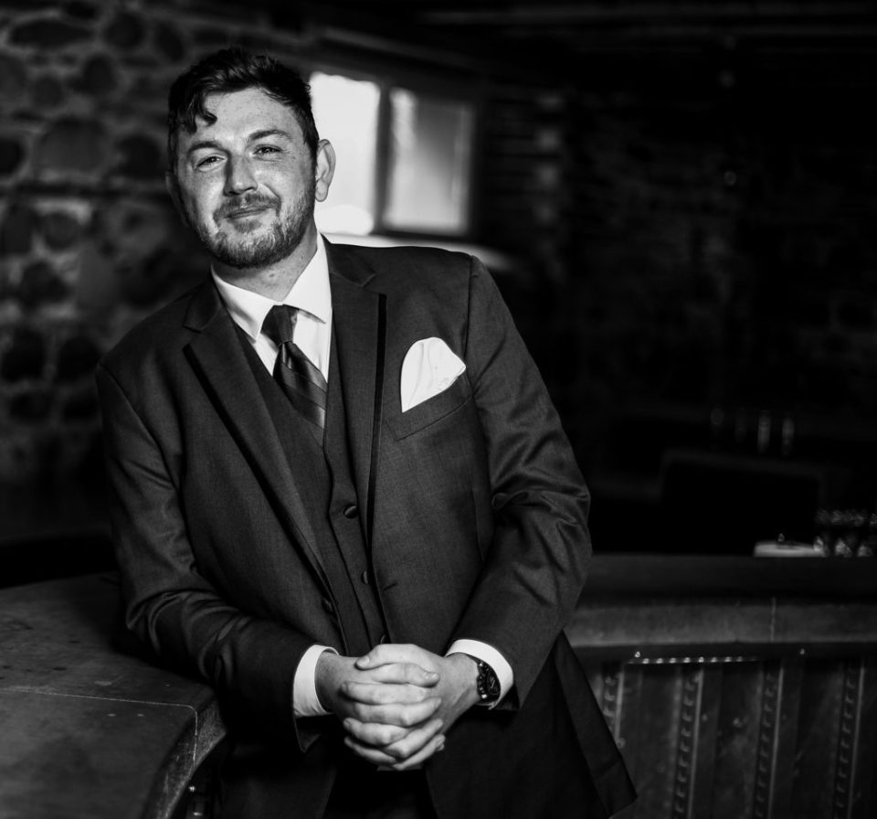 Solo portrait of the groom at the bar before his wedding at Quincy Cellars