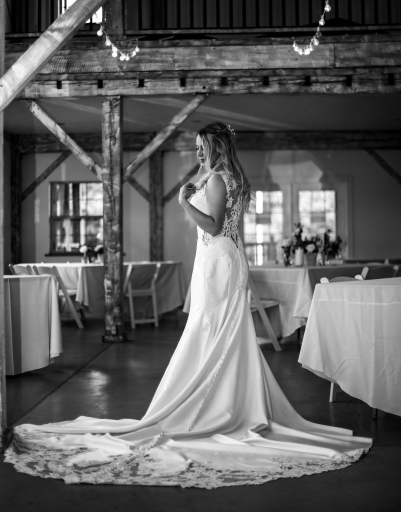 Solo portrait of bride inside the barn before guests arrive at her wedding at Quincy Cellars