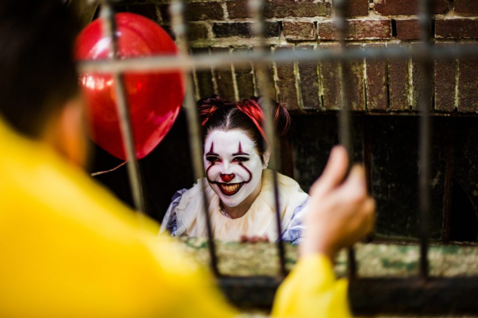Woman dressed as Pennywise smiles at man dressed as Georgie from the movie It