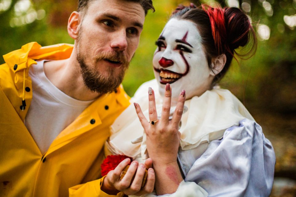 Couple shows off engagement ring at the end of Halloween engagement photo session