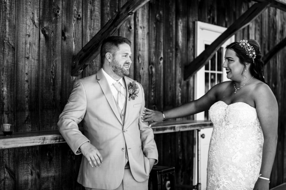 Bride touches groom's arm during first look portraits at Port Farms