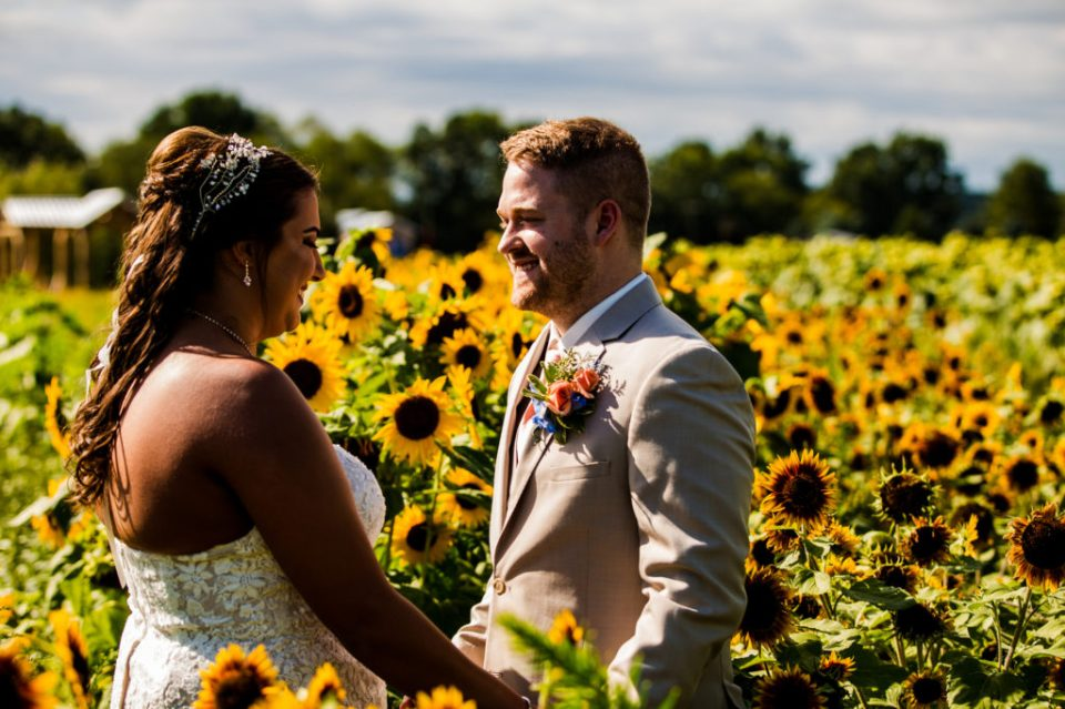 Bride and groom holding hands and smiling in the sunflower field at Port Farms