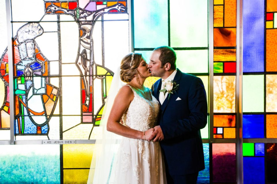 Bride and groom kiss next to stained glass at their St George Church wedding
