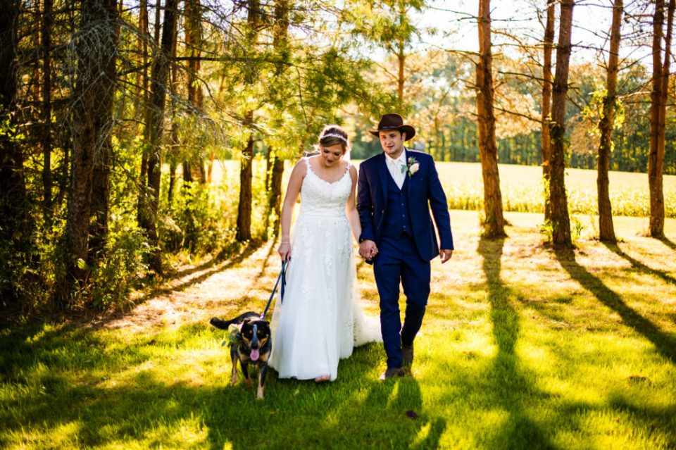 Bride and groom walk with their dog on family farm in Waterford PA