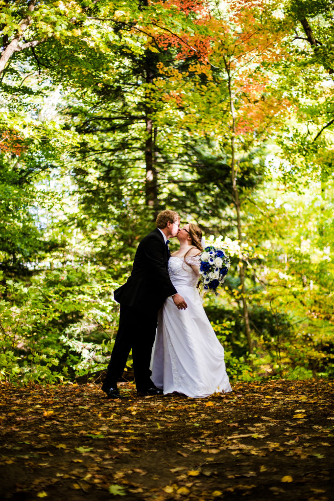 Bride and groom kissing in arboretum at Penn State Behrend
