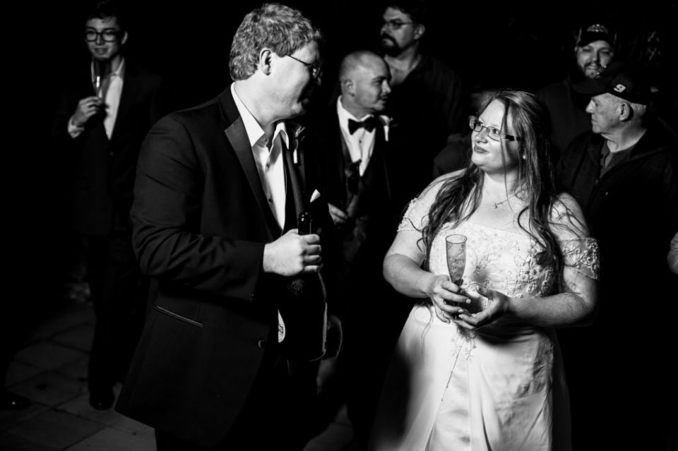 Bride and groom smile at each other while drinking champagne