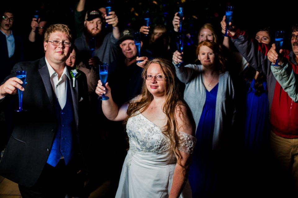 Bride, groom and their guests raise glasses of champagne in a toast at their home in Erie, PA