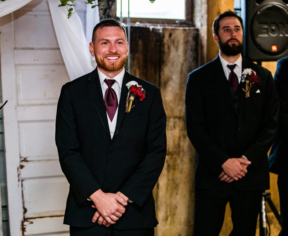 Groom grins heartily as his bride walks down the aisle at their Barn at Conneaut Creek wedding