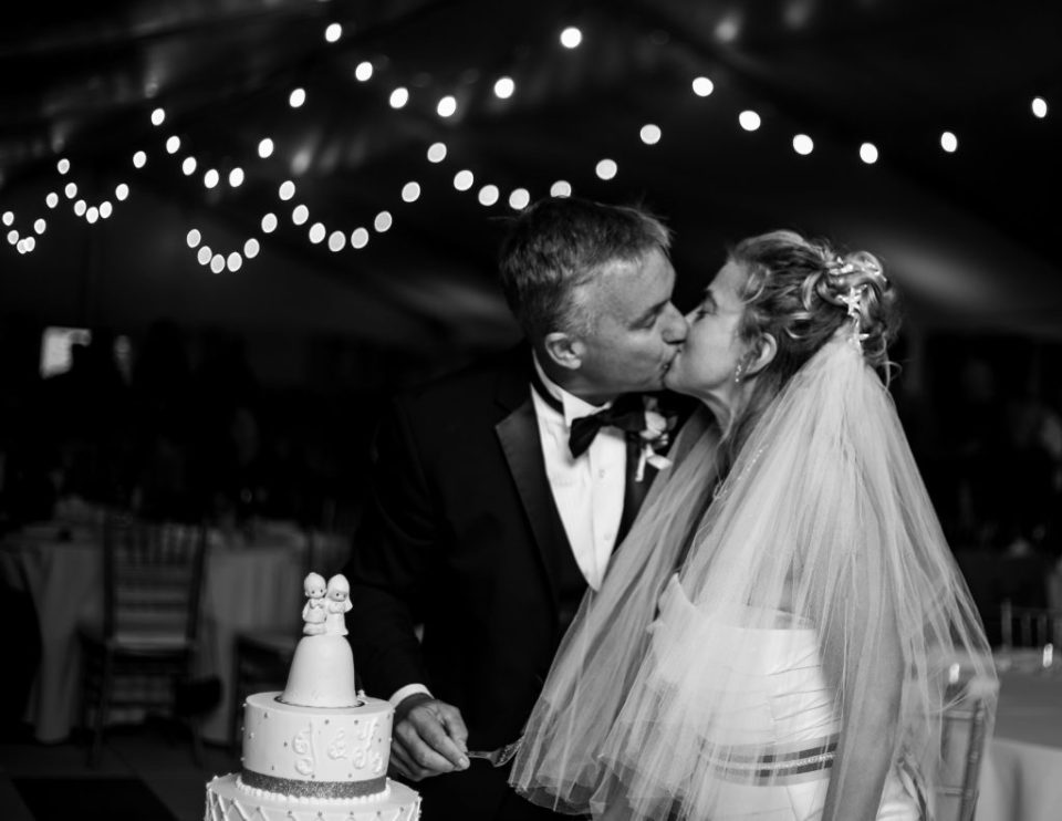 Bride and groom kissing as they prepare to cut the cake at their Anchor Plaza wedding