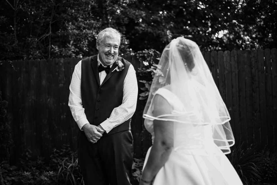 Groom smiles as he sees his bride during first look photos at their home in Erie, PA w