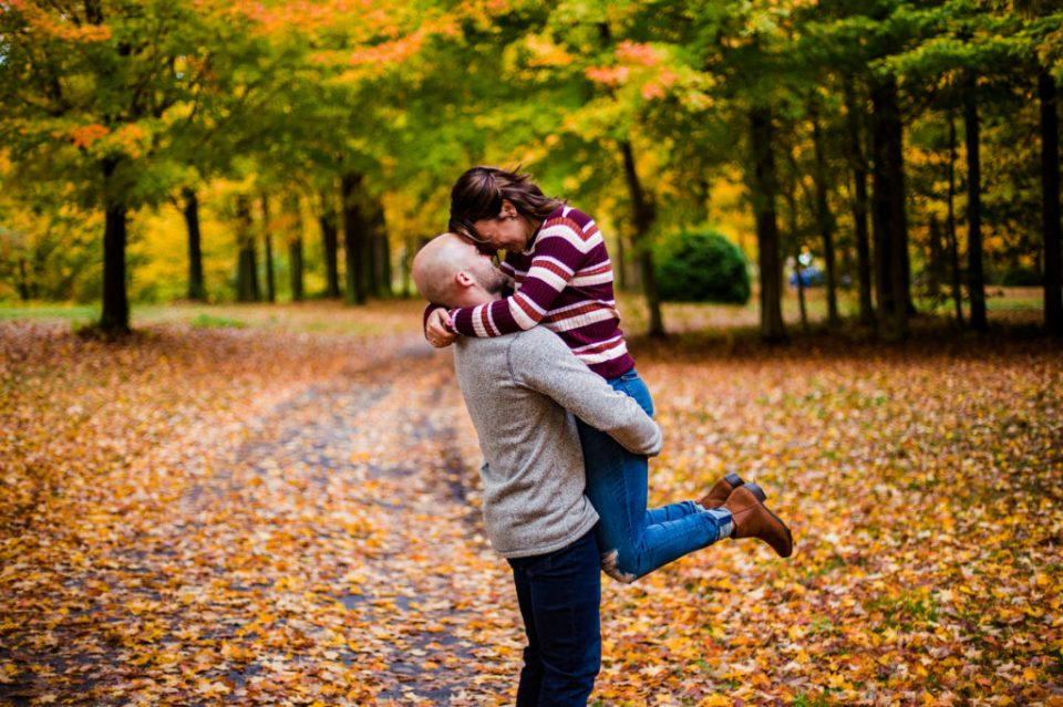 Man lifts fiancee in the air during Lake Erie Community Park engagement photos