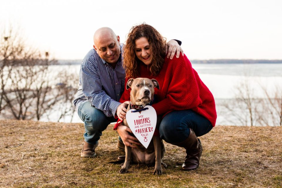 Couple poses with their dog wearing a save the date sign