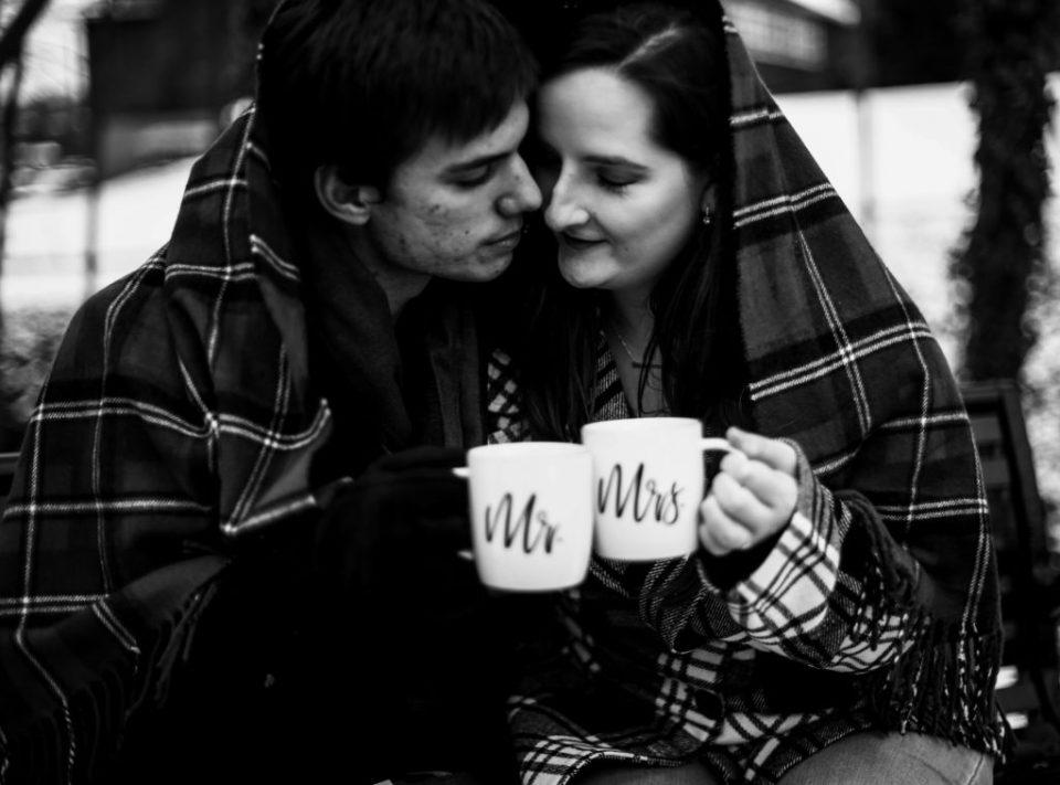 Couple huddle under a blanket holding mugs of hot chocolate