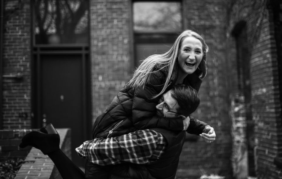 Man lifts laughing woman during engagement photos at Modern Tool Square in Erie PA