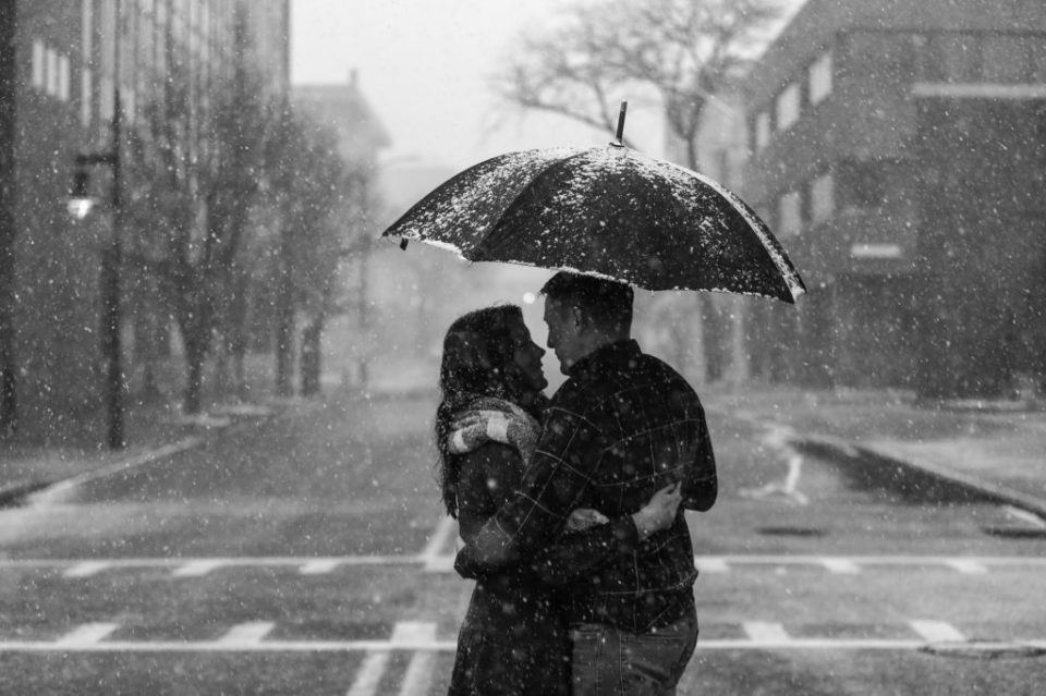 Couple stand under umbrella as it snows in downtown Erie engagement photo session