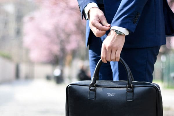 Man in suit adjusting the cuff of his sleeve, holding a briefcase.
