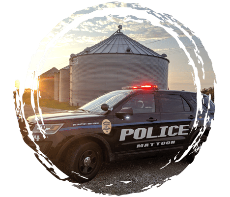 Police cruiser parked in front of grain bins with sun rising in the sky.