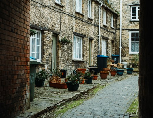 photo of cobblestone street in England with old houses and large plant pots