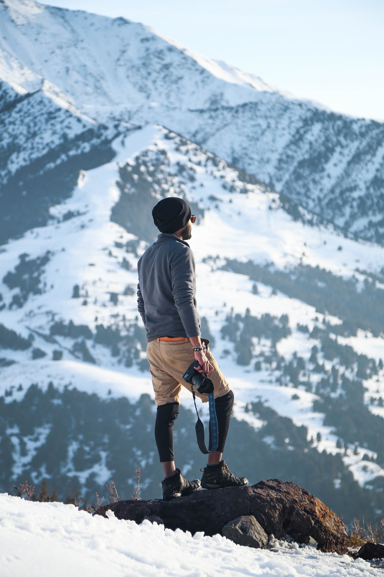 man standing at top of mountain looking for inspiration