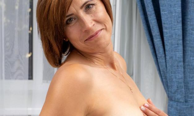 Stijlvolle oudere vrouw, kort haar en schaamhaar, gaat naakt op de bank