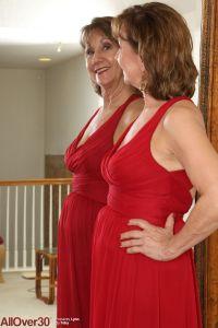 Knappe mature vrouw heeft een lange rode jurk aan