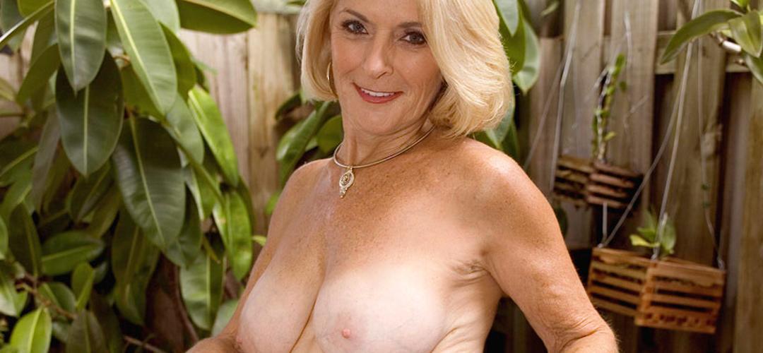 Stijlvolle oma, grote borsten, is aan het masturberen in de tuin