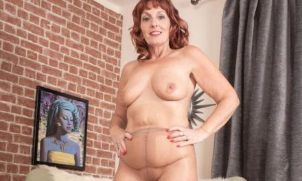 Mooie oude vrouw, rood haar en grote borsten, houdt haar panty's aan