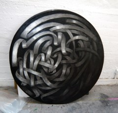 SPIRAL, 2008, black stone on wood, 120 cm diameter.