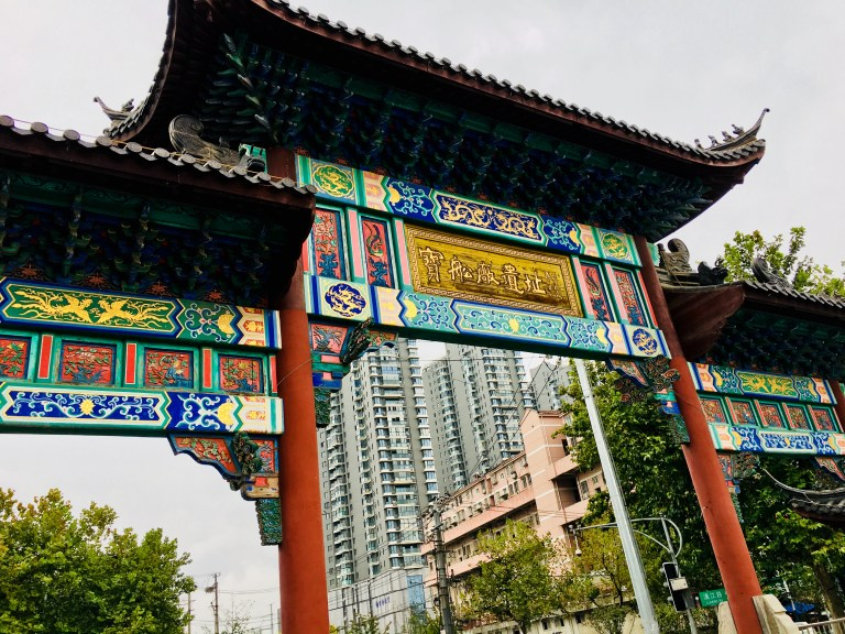 Typically old Chinese colourful arch structure with modern buildings behind it.
