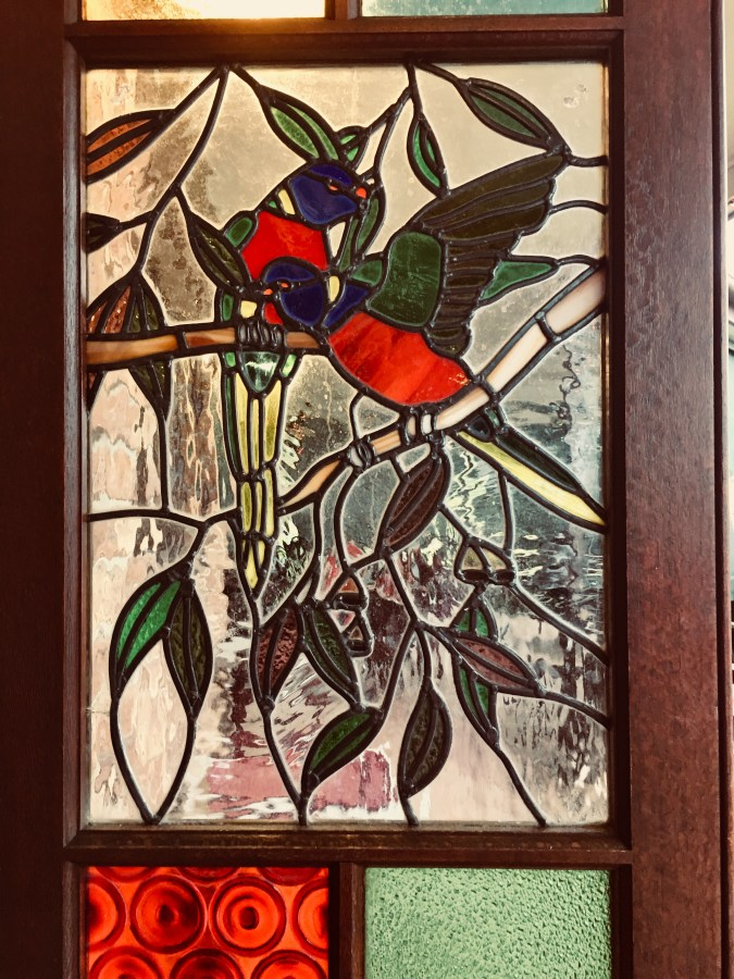 Stained glass window featuring a red parrots and leaves