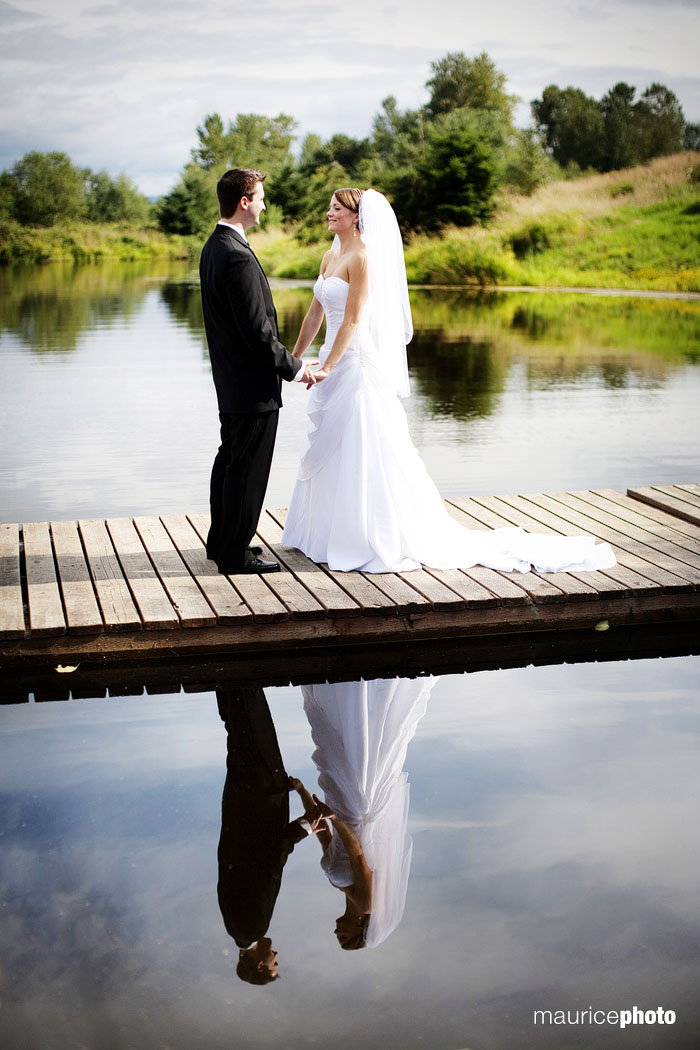 A portrait of a bride and groom on the dock at Lord Hill Farms